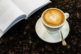 Coffee on the table and reading book — Stockfoto