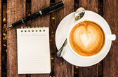 Open a blank white notebook, pen and cup of coffee on wood desk  — Stock Photo