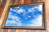 Vintage golden frame distortion hanging on wooden wall with land — Stock Photo