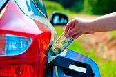 Female hand puts the car into the gas tank one hundred dollars — Stock Photo
