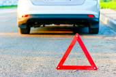 Red warning triangle and a car pull over to the side of the road — Stock Photo
