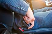 Driver in business suit fastens his seat himself automobile seat belt — Stock Photo