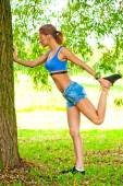 Beautiful girl doing warm-up at the tree park in sportswear — Stock Photo