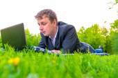 Man working with laptop lying on the lawn — Stock Photo