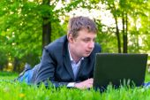 Businessman intently working on a laptop on the grass — Stock Photo