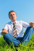 Happy businessman relaxes in a field in the lotus position — Stock Photo