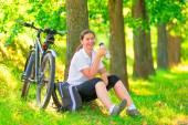 Gelukkig mooi meisje heeft een rust zitten in een boom met een fiets — Stockfoto