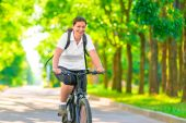 Joyful girl on a bicycle with a backpack — Stockfoto