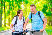 Morning walk in the park on bicycles couples — Stock Photo