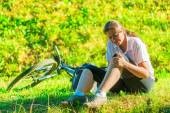Cyclist holds a his bruised knee while sitting on the lawn — Stock Photo
