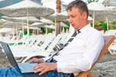 Manager working on a laptop on the beach — Stock Photo