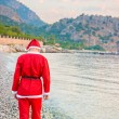 A man dressed as Santa Claus walks along the coast — Stock Photo #52852409