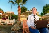 Manager i en skjorta och slips på stranden på en glasveranda — Stockfoto