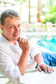 Portrait of a handsome businessman at the pool — Stock Photo