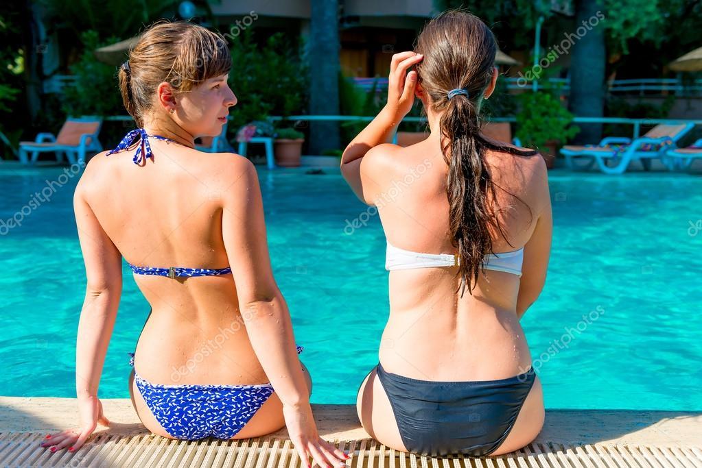 Chicas wo sentado en el borde de la piscina en un traje de for Bikini piscina