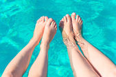 Two pairs of female legs in the pool — Stock Photo