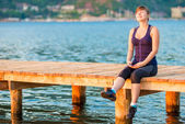 Pretty teenage girl sitting on a wooden pier and listening to mu — Foto de Stock