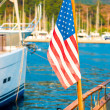 USA flag on the background of the masts of yachts in the port — Stock Photo #55865311
