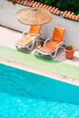 Sun loungers and parasols near the pool — Stock Photo
