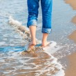 Barefoot man in jeans walking on the sea shore — Stock Photo #57018993