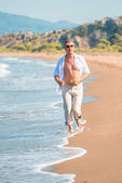 Male clothed in linen, runs along the seashore — Stock Photo