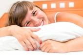 Laughing beautiful girl resting in bed — Stockfoto