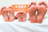 Family of three people sleeping in one bed, feet close-up — Stock Photo