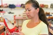 Женщина выбирает красную обувь в магазине перед покупкой — Стоковое фото