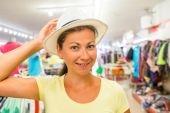 Woman with a beautiful smile at the store chooses hat  — Stock Photo