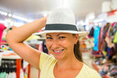 Pretty girl tries on a white hat in the store — Stock Photo