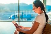 Jong meisje met documenten in de afdrukwachtrij aan boord van het vliegtuig — Stockfoto