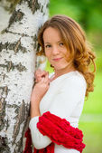 Young beautiful girl with red hair in a birch — Stock Photo