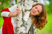 Beautiful young girl looks out from behind a birch — Stock Photo