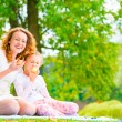 Young mother and her daughter eating apples in the park — Stock Photo #60193947