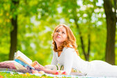 Pensive look beautiful young girl with an interesting novel — Stock Photo