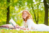 Mädchen mit einem guten Buch Lachen auf dem Rasen im Park Sommer — Stockfoto