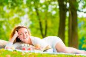 Brown-eyed girl with apples and a book in the park — Стоковое фото