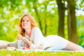 Thoughtful beautiful girl with ripe apple in the park — Stockfoto