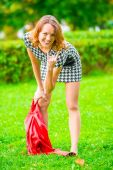 Impish girl posing on the grass in the park — Stock Photo
