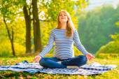 Pregnant woman in a lotus position performs breathing exercises outdoors — 图库照片