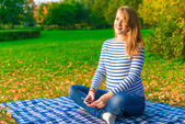 Pregnant woman listening to classical music in the autumn park — ストック写真