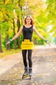 Активная молодая девушка, катающаяся на роликах в осеннем парке — Стоковое фото