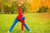 Morning warm up of a young athlete on a glade in park in autumn — Stock Photo