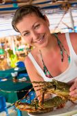 Girl holding a raw lobster and smiling — Стоковое фото