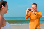 Husband photographing his wife at the resort — Stock Photo