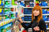 Girl in shop chooses Christmas decorations — Foto Stock