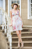 Girl in the hat and summer sundress on the stairs — Stock Photo