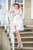 Portrait of a girl standing on the stairs in sundress — Stock Photo