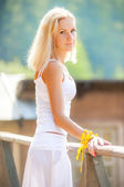 Beautiful young girl in a white sundress looking at the camera — Stock Photo