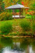 Gazebo in the empty autumn park near the pond — Stock Photo